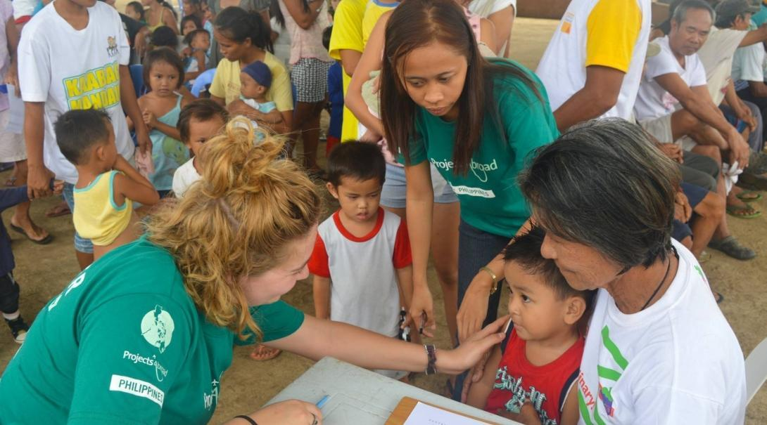 An intern from Projects Abroad is seen talking a to a young boy and his mother during her public health internship in the Phillippines.